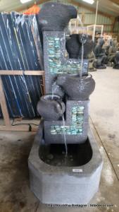 Fontaine eau béton avec galets verts